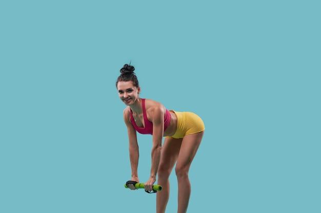 승진을위한 복사 공간이 파란색 표면에 아령으로 운동하는 섹시한 여성 피트니스 강사