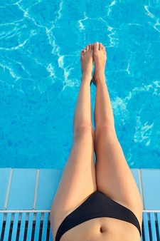 Sexy female legs at blue water of swimming pool. sun protection.sun cream. skin and body care.