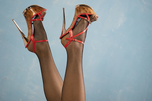 Sexy female legs in high heel black shoes and fishnet stockings on blue