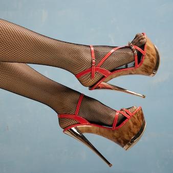 Сексуальные женские ножки в черных туфлях на высоком каблуке и чулках в сеточку на синем