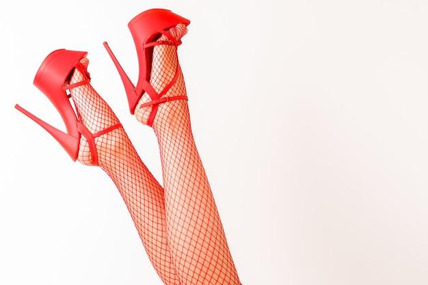 Сексуальные женские ножки в красных туфлях для стриптиза на высоких каблуках и чулках в сеточку.
