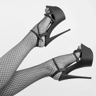 하이힐 스트립 신발과 망사 스타킹에 섹시한 여성 다리