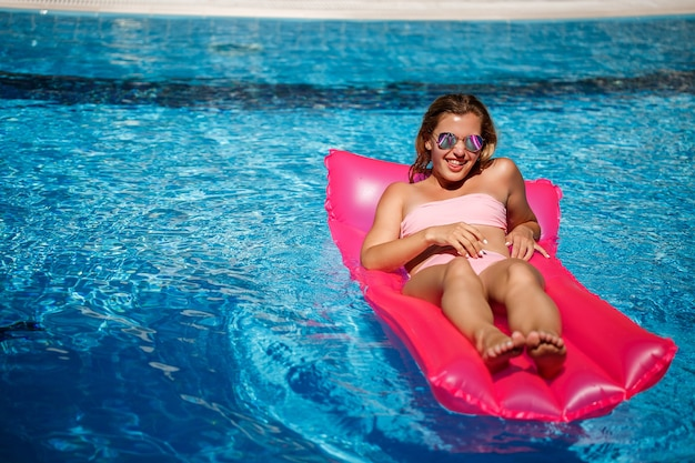 Sexy female model resting and sunbathing on a mattress in the pool. woman in a pink bikini swimsuit floating on an inflatable pink mattress. spf and sunscreen