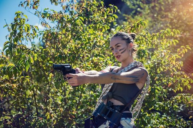 섹시한 여성 모델은 여름 야외, 군대 개념에서 총을 든 짧은 천을 착용합니다.