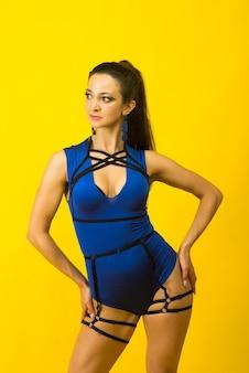 노란색 배경에 파란색 바디 슈트와 하이힐을 입고 섹시한 여성 극 댄서