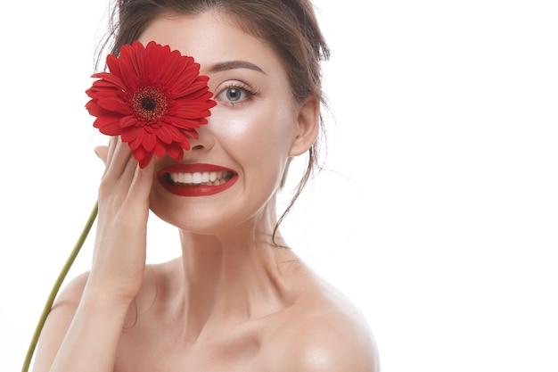 カメラに微笑んで、赤で隔離の赤い花で片目を閉じるセクシーな女性