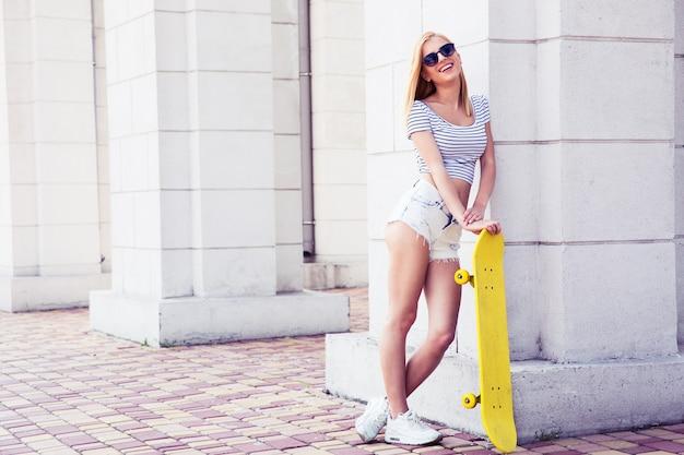 スケートボードを保持しているサングラスのセクシーな女性のティーンエイジャー