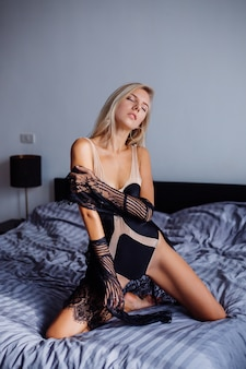 베이지 색 바디와 검은 색 투명 레이스 케이프의 일출 빛 침실에서 섹시한 맞는 유럽 여성