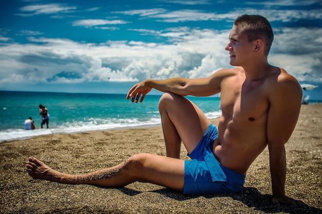 Сексуальная подходящая мужская модель, лежащая в воде на пляже
