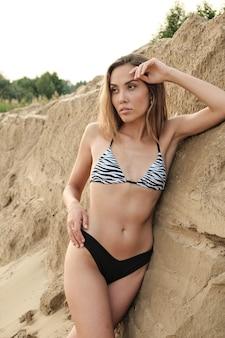 Сексуальная соблазнительная женщина пригонки в бикини на песчаном пляже, расслабляясь, загорая. молодая стройная привлекательная азиатская женщина в купальнике, отдыхая в одиночестве на природе. летний отдых, релаксация, отдых, сексуальность