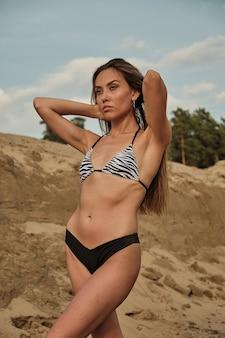Сексуальная соблазнительная женщина в бикини, расслабляющаяся, загорая в одиночестве на песчаном пляже