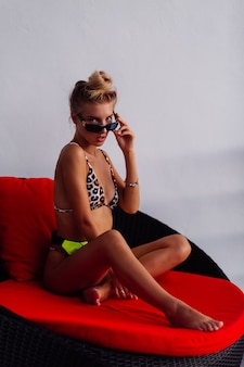 Sexy fit tanned european fashion blogger woman in tiny leopard bikini, neon yellow green waist bag on red pillow sofa