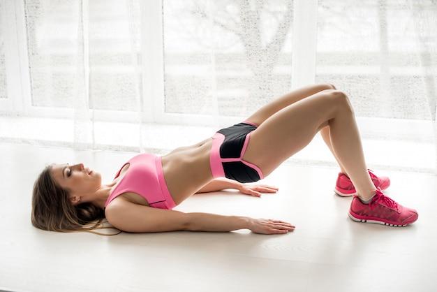 섹시 피트니스 운동 선수는 스튜디오에서 운동 다리를 수행