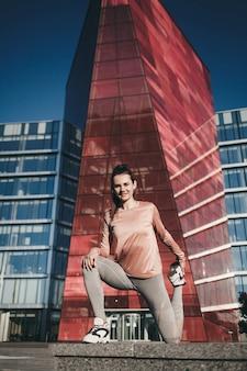 Сексуальная фитнес-спортсменка выполняет упражнения и разминку на фоне здания