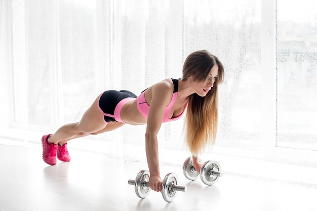Sexy fitness athlete performs push-ups in the studio with dumbbells