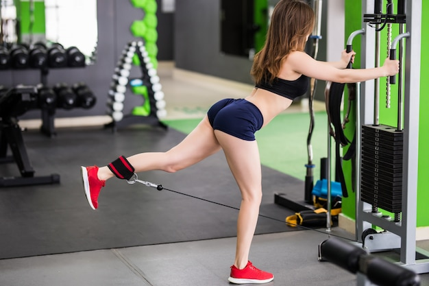Sexy fitness instructor with strong fit body make exercises in gym with sport simulator
