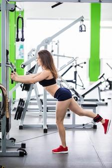 강한 몸매를 가진 섹시한 피트니스 강사는 스포츠 시뮬레이터로 체육관에서 다리 운동을합니다.