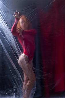 Sexy girl athlete in a red bodysuit on a dark background.