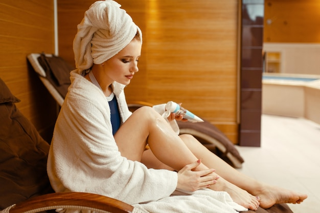 Sexy girl in bathrobe and towel on the head applying cream in spa chair