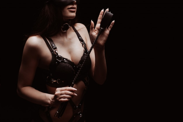 Sexy girl in a black beautiful bra playing with a whip. the concept of bdsm