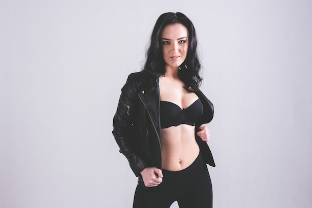 Sexy girl in black leather jacket against a bright background