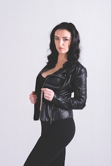 Sexy girl in black leather jacket stands on a light background