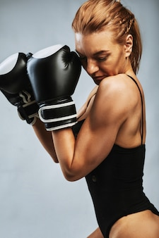 Sexy girl boxer with athletic beautiful figure in black swimsuit and boxing gloves on a gray background challenge yourself
