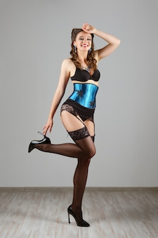 Sexy girl in burlesque corset and lingerie posing against wall
