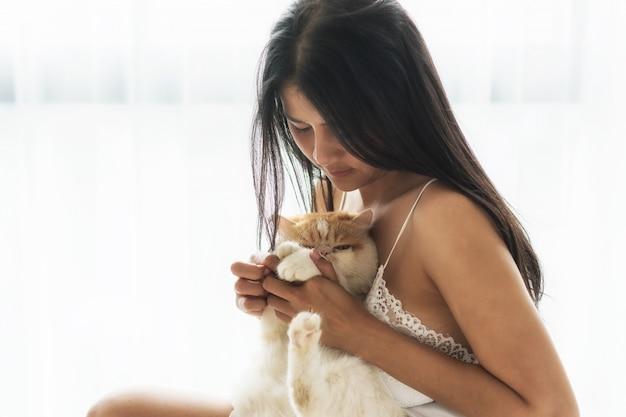 セクシーな女の子の寝室で猫を抱きしめる