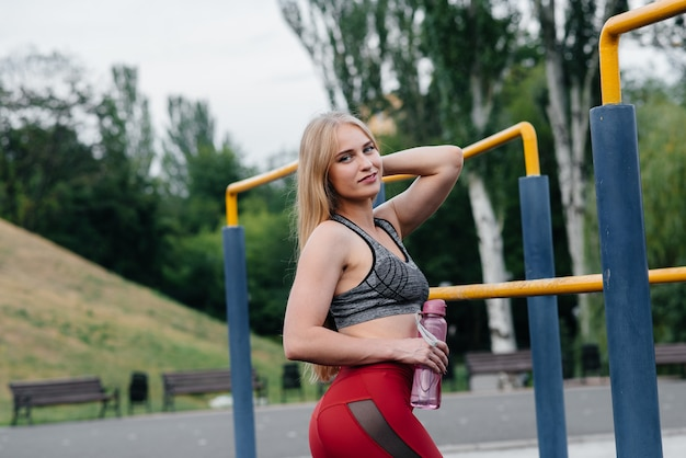 セクシーな女の子はスポーツをし、屋外で水を飲みます。フィットネス。健康的な生活様式