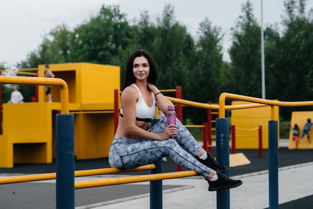 Sexy girl does sports and drinks water in the open air. fitness. healthy lifestyle