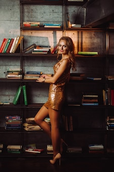 Sexy girl in a gold dress on the background of books in the library.model with long hair and red lipstick in the interior.