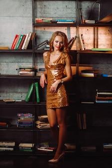 図書館の本の背景に金のドレスを着たセクシーな女の子。内部に長い髪と赤い口紅のモデル。