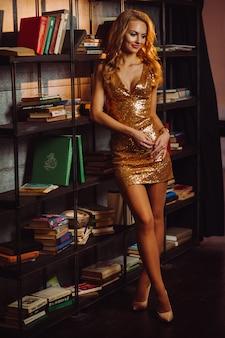 도서관에서 책의 배경에 골드 드레스에 섹시 한 여자. 긴 머리와 내부에 빨간 립스틱 모델.