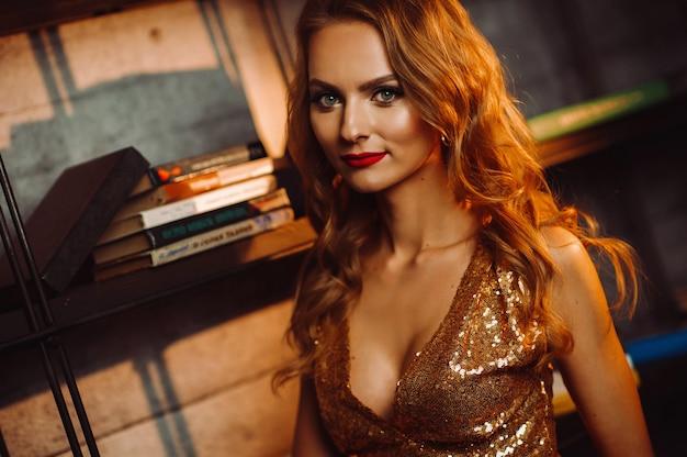 Сексуальная девушка в золотом платье на фоне книг в библиотеке. модель с длинными волосами и красной помадой в интерьере.