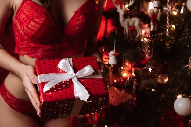 Сексуальная девушка в красном бюстгальтере и трусиках рядом с елкой. концепция эротического деда мороза с подарком в руках