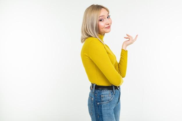 コピースペースと白い背景にタイトフィットの黄色いブラウスとジーンズのかわいい笑顔でセクシーな女の子