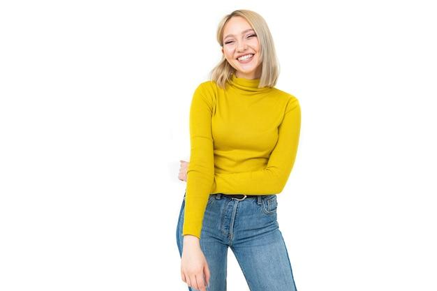 Сексуальная девушка в обтягивающей желтой блузке и джинсах мило улыбается на белом фоне с копией пространства.