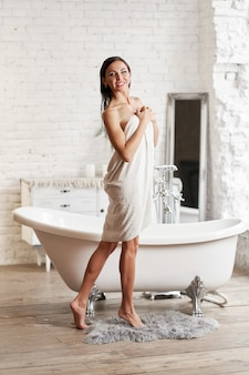 Сексуальная девушка в белом пальто собирается принять ванну. девушка в халате после принятия ванны.