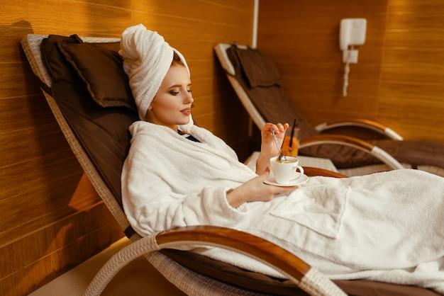 Сексуальная девушка в халате и полотенце на голове, расслабляясь с чашкой кофе в кресле спа.