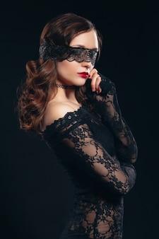 黒のランジェリーでセクシーな女の子。彼女の顔に目隠しマスクを持つエロティックな魅力的な魅力的な女性。完璧なお尻と美しいメイク