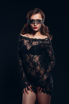 검은 란제리에 섹시한 여자. 그녀의 얼굴에 눈가리개 마스크와 에로틱 한 매력적인 매력적인 여자. 완벽한 엉덩이와 아름다운 메이크업