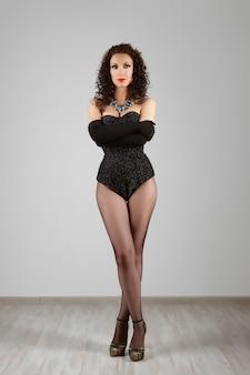 Сексуальная девушка в бурлескном корсете и нижнем белье позирует у стены
