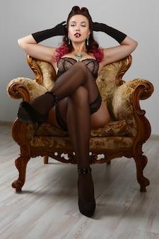 Сексуальная девушка в корсете и нижнем белье позирует в кресле