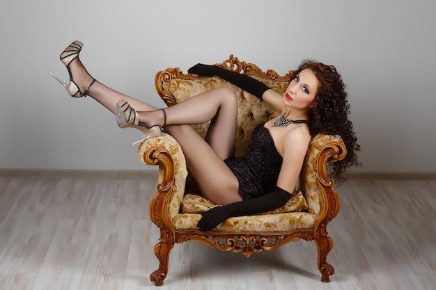 Сексуальная девушка в корсете и нижнем белье сидит на винтажном кресле