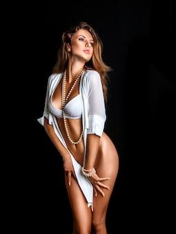 Сексуальная девушка в нижнем белье на черном фоне в студии