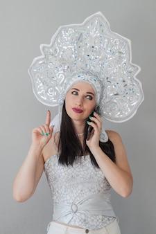 새해 러시아 kokoshnik의 섹시한 여자 그녀의 손에 전화가있는 눈의 여왕은 감정을 보여줍니다