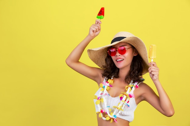 Sexy girl is holding watermelon and mango ice cream while wearing glasses and hat in summer hot weather on yellow wall.