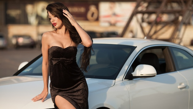 Sexy girl is shown with long black dress and red lips near white car. curly hair. fashion shot.