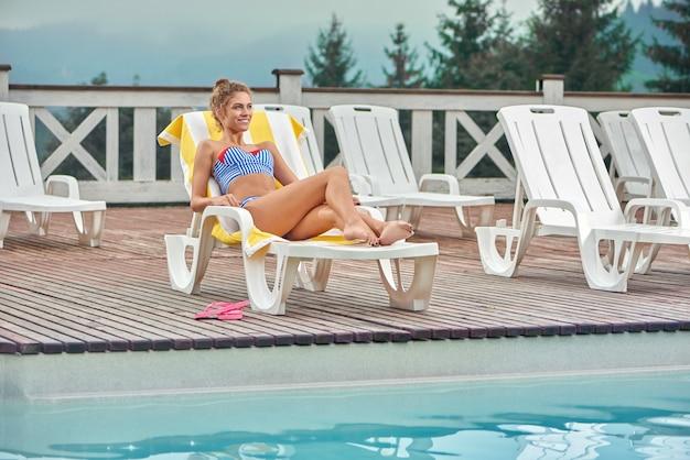 プールの近くのタオルで白いラウンジャーで横になっているセクシーな女の子。